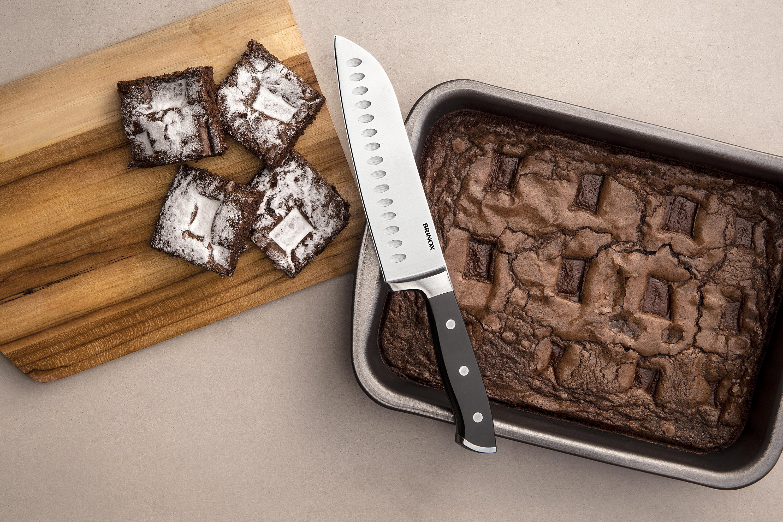 Assadeira com antiaderente Pro-flon. Na foto temos um brownie de chocolate na forma e em uma tábua de maneira alguns pedaços cortados. Ao lado dos brownies tem uma faca de corte Santoku.