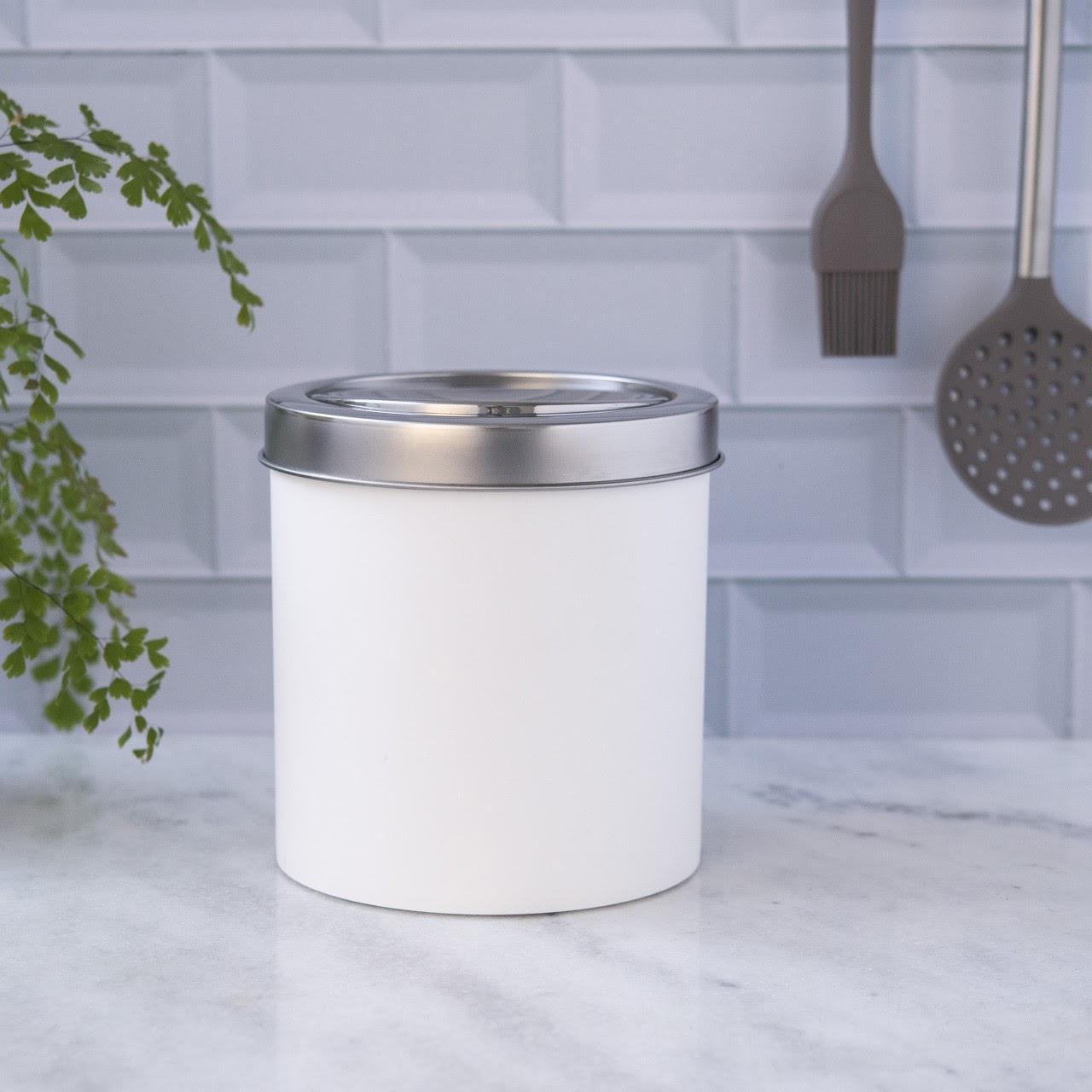 Lixeira basculante Decorline na cor branca. Está em cima de uma bancada da cozinha.