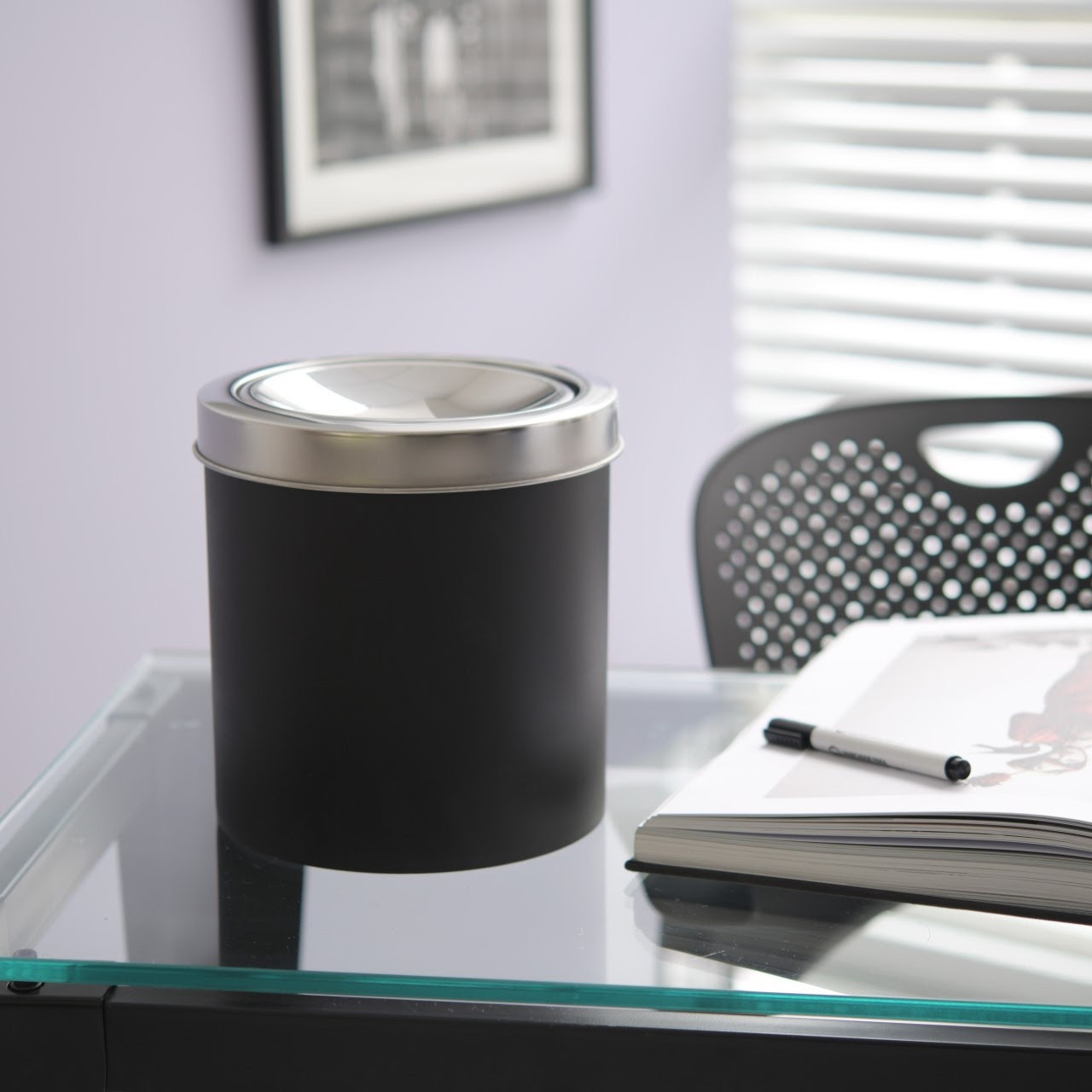 Lixeira basculante Decorline na cor preto. Ela está em cima de uma mesa de vidro de um escritório.