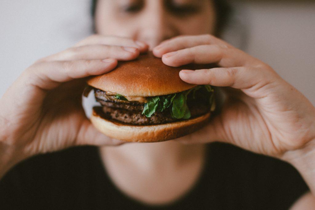 Na imagem temos uma mulher segurando um hambúrguer na frente do rosto.